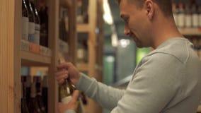Porträt des netten Mannes nimmt Weißweinflasche im Geschäftsabschluß herauf Kunden wählt Getränk im Alkoholgeschäft stock footage