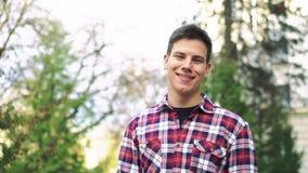 Porträt des netten Mannes seine Uhr betrachtend, stehend auf dem Baumhintergrund stock video
