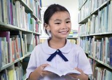 Porträt des netten Schulmädchens lächelnd beim Ablesen Stockfotografie