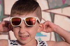 Porträt des netten tragenden gestreiften Hemdes und der Sonnenbrille des kleinen Jungen Stockbilder