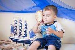 Porträt des netten und glücklichen kaukasischen kleinen Jungen, der sorgfältig auf einen großen Cockleshell hört lizenzfreie stockfotografie