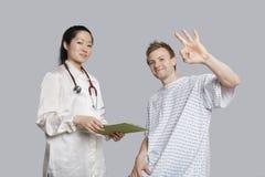 Porträt des Patienten o.k. gestikulierend mit Doktor, der ein Klemmbrett hält Stockfotografie