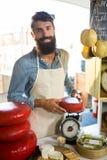 Porträt des Personals Gouda-Käse am Zähler wiegend Stockfotografie