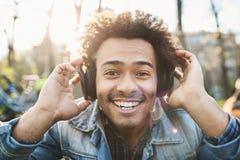 Porträt des positiven erwachsenen dunkelhäutigen Mannes, der breit beim Sitzen im Park, hörend Musik in den Kopfhörern lächelt un stockbild