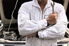 Porträt des professionellen jungen Mechanikermannes im einheitlichen haltenen Schlüssel gegen Auto in der offenen Haube an der Re Stockbild
