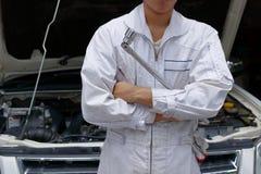 Porträt des professionellen jungen Mechanikermannes im einheitlichen haltenen Schlüssel gegen Auto in der offenen Haube an der Re Stockbilder