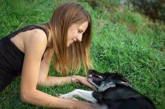 Porträt des recht attraktiven Mädchens, das draußen Zeit mit ihrem aktiven lustigen weißen und schwarzen Hund während des Sommert Lizenzfreies Stockfoto