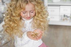 Porträt des recht blonden kleinen Mädchens betrachtet ein Konfetti auf Hände im Weihnachten Stockfotografie
