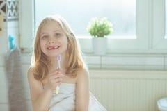 Porträt des recht kleines Kindermädchens mit weißem Tuch nach Show Stockbilder
