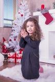 Porträt des recht süßen kleinen Mädchens nahe einem Kamin im Weihnachten stockfotos