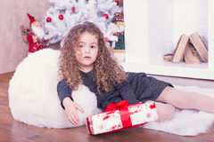 Porträt des recht süßen kleinen Mädchens nahe einem Kamin im Weihnachten lizenzfreie stockfotografie