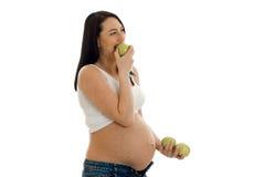 Porträt des recht schwangeren Brunette im Hemd isst die grünen Äpfel, die auf weißem Hintergrund lokalisiert werden Lizenzfreie Stockbilder
