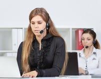 Porträt des recht weiblichen Informationsstellenangestellten mit Kopfhörer am Arbeitsplatz Stockfotografie
