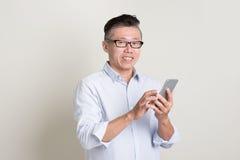 Porträt des reifen asiatischen Mannes, der intelligentes Telefon verwendet Stockfoto