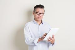 Porträt des reifen asiatischen Mannes, der Tablet-Computer verwendet Stockfotografie