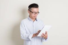 Porträt des reifen asiatischen Mannes, der Tabletten-PC verwendet Lizenzfreie Stockfotografie