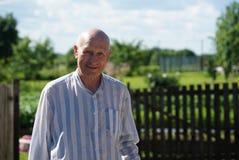 Porträt des reifen lächelnden Mannlandwirts im Garten Stockfotografie