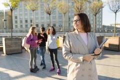 Porträt des reifen lächelnden weiblichen Lehrers in den Gläsern mit Klemmbrett, outdor mit einer Gruppe Jugendlichstudenten lizenzfreie stockfotos
