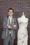 Porträt des reifen männlichen Modedesigners, der nahe bei der Attrappe des Schneiders steht lizenzfreies stockfoto