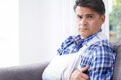 Porträt des reifen Mannes mit dem Arm im Riemen zu Hause lizenzfreies stockbild