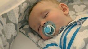 Porträt des reizend Babys schläft in einer Krippe stock video footage