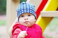 Porträt des reizenden Babys Stroh auf Spielplatz kauend Stockbild