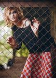 Porträt des reizenden Grungerockmädchens im karierten Rock und in der Strickjacke, die hinter metallischem Gitter steht stockbilder