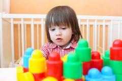 Porträt des reizenden kleinen Jungen, der zu Hause Plastikblöcke spielt Stockfotografie