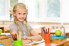 Porträt des reizenden Schulmädchens im Klassenzimmer Betrachten der Kamera Stockfotos