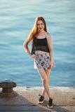 Porträt des rothaarigen Mädchens auf dem Seehintergrund Lizenzfreies Stockbild
