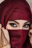 Porträt des schönen arabischen Mädchens, das ihr Gesicht versteckt Stockfotografie