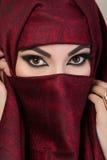 Porträt des schönen arabischen Mädchens, das ihr Gesicht versteckt Lizenzfreie Stockfotografie