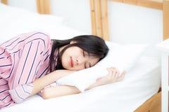 Porträt des schönen asiatischen Schlafes der jungen Frau, der im Bett mit Kopf auf dem Kissen bequem und glücklich liegt stockfotografie