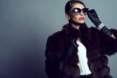 Porträt des schönen bezaubernden vorbildlichen tragenden Zobelmantels, der Sonnenbrille, der Handschuhe und des Schmucks stockfotografie