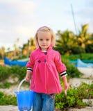 Porträt des schönen blond-haarigen Mädchens, das auf dem Strand spielt Lizenzfreie Stockbilder