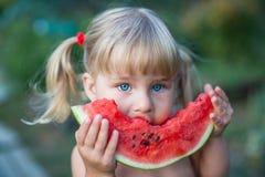 Porträt des schönen blonden kleinen Mädchens mit zwei Pferdeschwänzen Wassermelone essend stockfotos