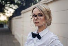Porträt des schönen blonden Mädchens in den Gläsern stockfotografie