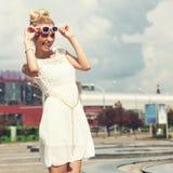Porträt des schönen blonden Mädchens in der Sonnenbrille auf blauem Himmel des Hintergrundes Stockbild