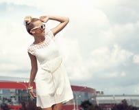 Porträt des schönen blonden Mädchens in der Sonnenbrille auf blauem Himmel des Hintergrundes Stockfotos