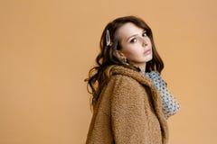 Porträt des schönen brunette Mädchens im beige Pelzmantel auf beige Hintergrund lizenzfreies stockbild