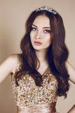 Porträt des schönen Brunettemädchens im luxuriösen Pailletten-Kleid und in der Krone Lizenzfreies Stockbild
