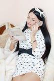 Porträt des schönen Brunettemädchens mit weißem Band auf Hauptleseinteressantem Buch sprechend auf dem glücklichen Lächeln des Ha Stockbild