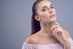 Porträt des schönen dunkelhaarigen jungen Modells mit perfekter Haut und nasser Akt bilden auf grauem Hintergrund Stockfoto