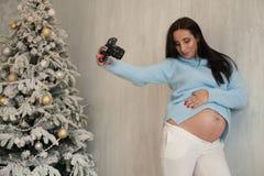 Porträt des schönen Fotografen der schwangeren Frau in einer Fotoaufnahme stockfoto
