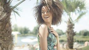 Porträt des schönen jugendlichen afroen-amerikanisch Mädchens auf dem tropischen Strand, der zu einer Kamera aufwirft Stockfotografie