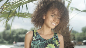 Porträt des schönen jugendlichen afroen-amerikanisch Mädchens auf dem tropischen Strand, der zu einer Kamera aufwirft Lizenzfreies Stockbild