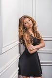 Porträt des schönen jungen blonden Mädchens im schwarzen Kleid Lizenzfreie Stockfotos