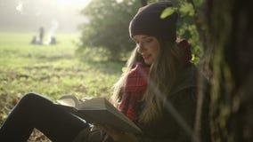 Porträt des schönen jungen kaukasischen Mädchens, das ein Buch im Park im Herbst liest stock footage