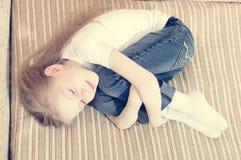 Porträt des schönen jungen Mädchens, das auf das Bett sich umarmt lächelnd legt, mustert geschlossenes u. das Träumen Lizenzfreie Stockfotos