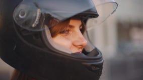 Porträt des schönen jungen rothaarigen Frauenmotorradfahrers im Sturzhelm bei Sonnenuntergang stock video